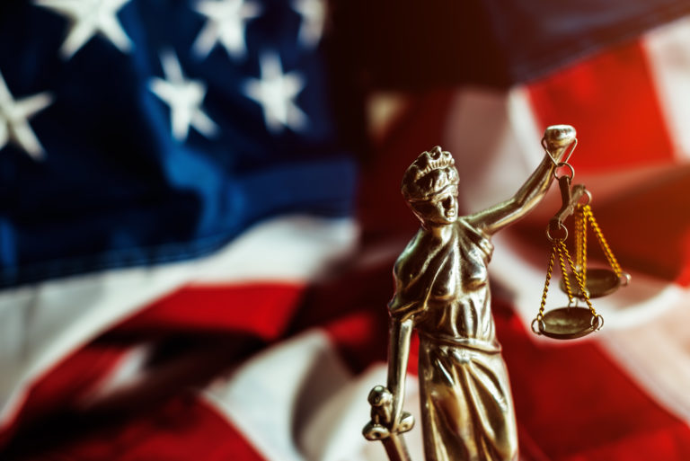 Lady Justice in front of American Flag