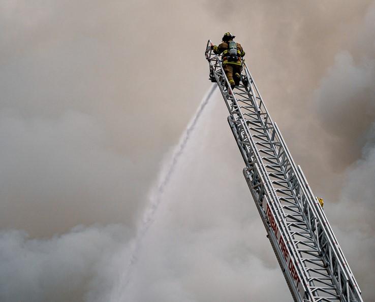 Firefighter On Ladder Spraying Hose
